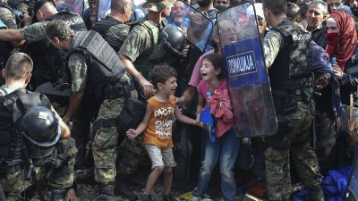 epa04891557 Children cry as migrants waiting on the Greek side of the border break through a cordon of Macedonian special police forces to cross into Macedonia, near the southern city of Gevgelija, The Former Yugoslav Republic of Macedonia, 21 August 2015. Macedonian police clashed with thousands of migrants attempting to break into the country after being stranded in no-man's land overnight, marking an escalation of the European refugee crisis for the Balkan country.  EPA/GEORGI LICOVSKI